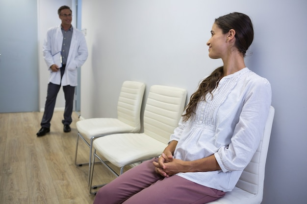 Woman looking at dentist while sitting on chair