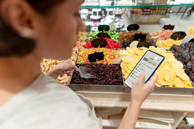 Woman looking for different goodies on her shopping list on a smartphone