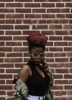 Женщина смотрит вниз перед кирпичной стеной