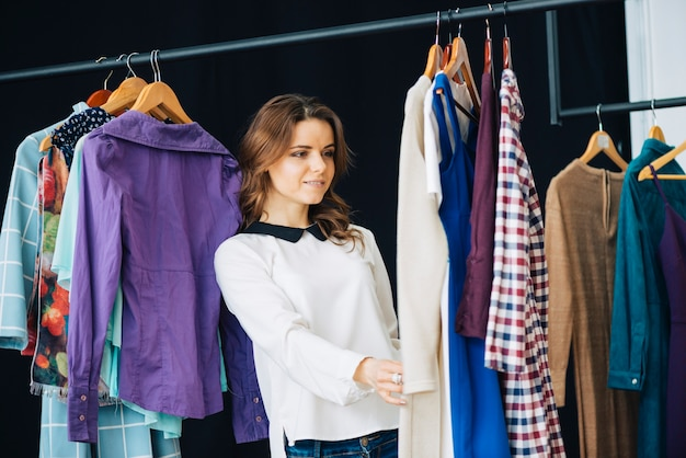 Woman looking at dresses on clothes rail