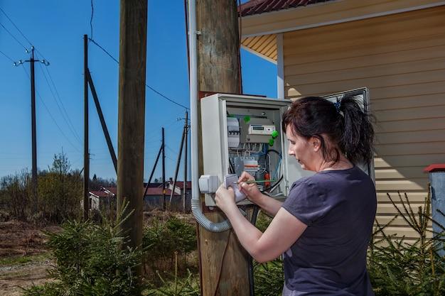 Женщина ищет данные электрического счетчика в распределительном устройстве, установленном на деревянном столбе возле фермерского дома в сельской местности.