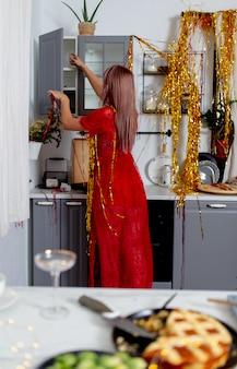 パーティーの後、キッチンで何かを探している女性