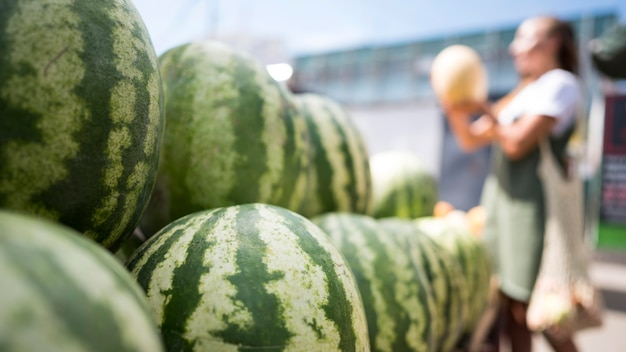 Woman looking for a fresh watermelon with copy space