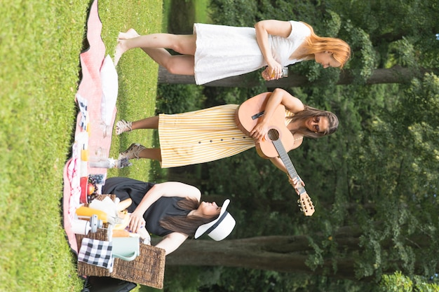 Woman looking at friend playing guitar on picnic