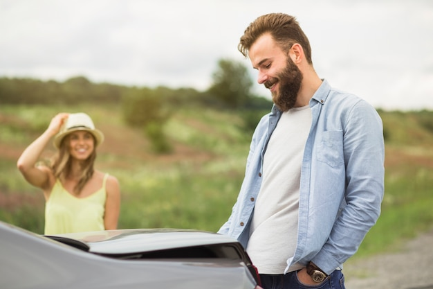 Woman looking at handsome man standing near the car at outdoors