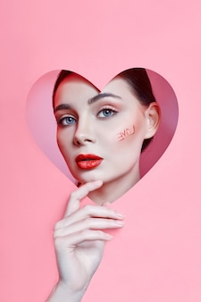 Woman looking in the heart hole, bright beautiful makeup, big eyes