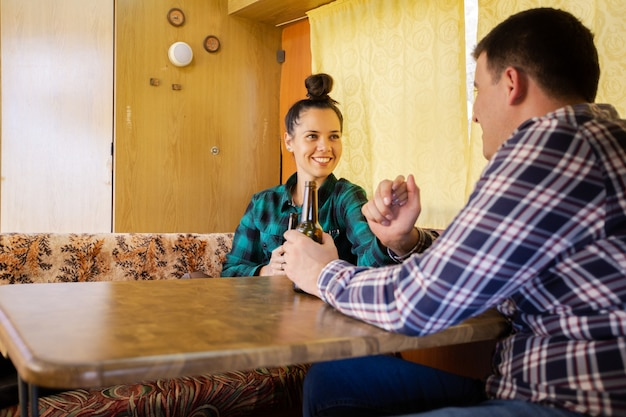 Woman looking at her boyfriend standing at table in retro camper. happy faces