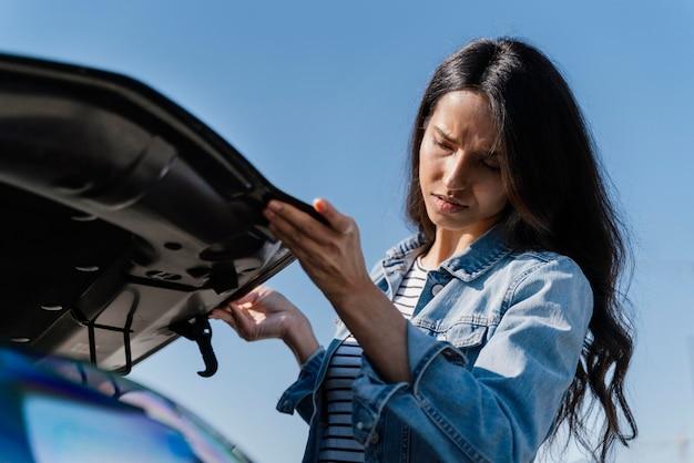 Donna che guarda la sua auto per risolvere un problema