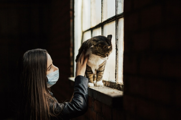 Woman looking at her cat. they are standing near a window in a protective mask.