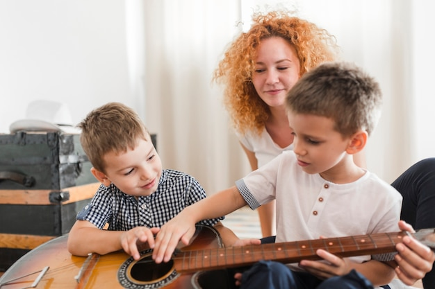 Woman looking at her children playing guitar