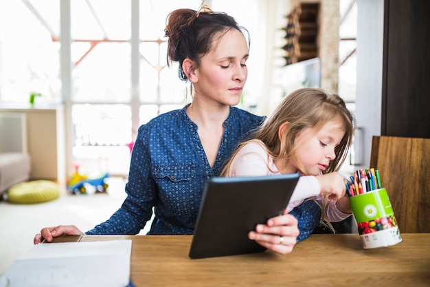 Woman looking at her daughter choosing pencil while holding digital tablet