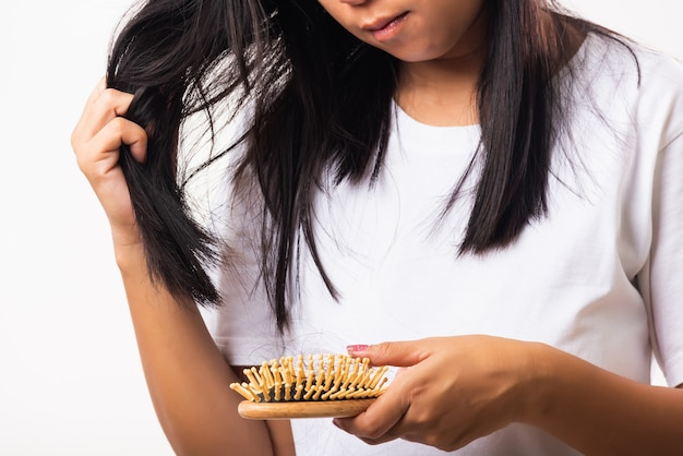 Женщина смотрит ее разрушенные волосы, держа расческу