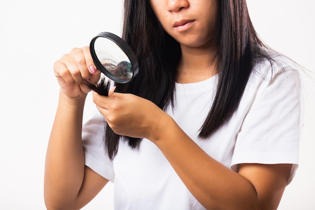 Woman looking her destroyed hair with magnifying glass