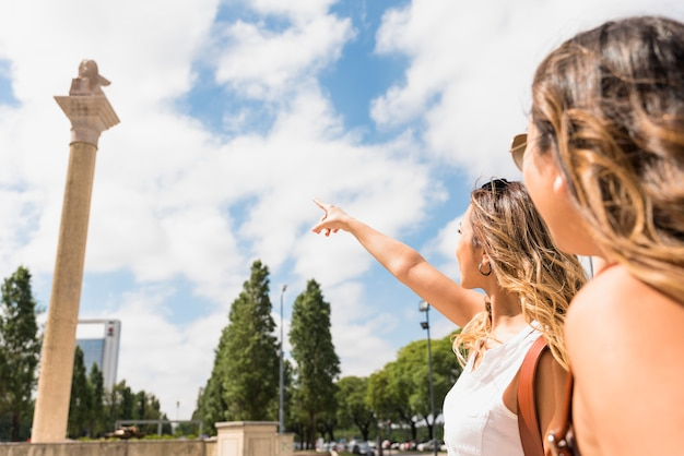 Woman looking at her female friend pointing the finger at pillar in the park