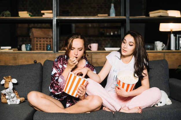 Woman looking at her friend taking popcorn from her bucket