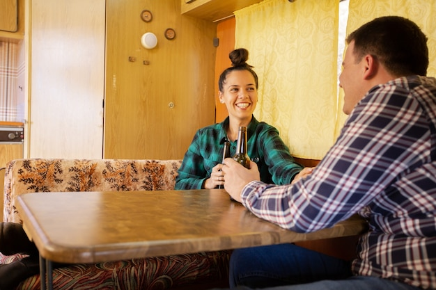 Woman looking at her lover and smiling stands at table in retro camper. relax atmosphere