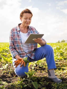 Woman looking at her tablet while holding some carrots