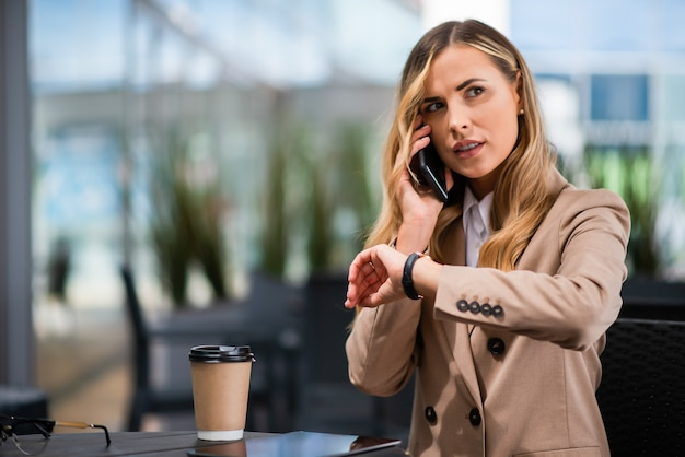 Woman looking at her watch while talking on her cellphone