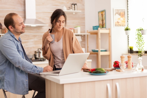 Woman looking at husband laptop while he is working in kitchen. girlfriend holding cup of coffee. happy loving cheerful romantic in love couple at home using modern wifi wireless internet technology