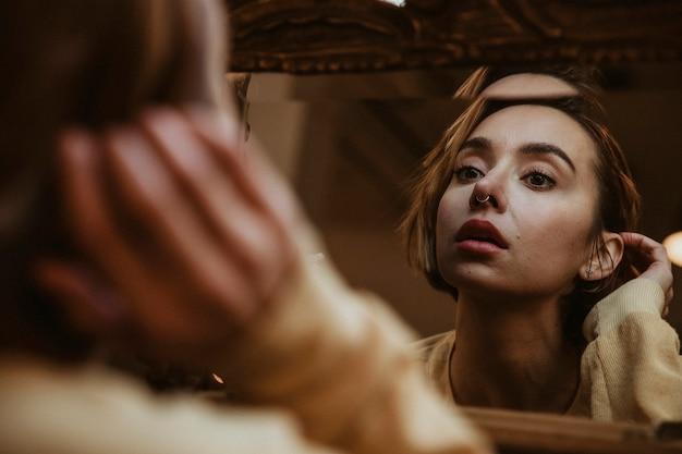 Женщина смотрит в зеркало в отчаянии