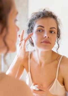 Женщина смотрит в зеркало и наносит крем на лицо