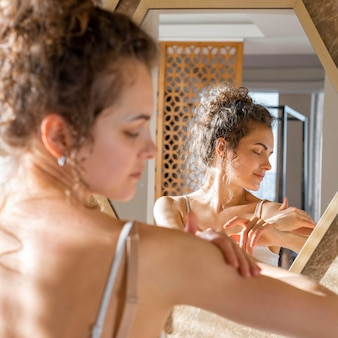 鏡を見て、手にクリームを塗る女性