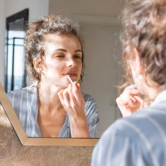 Женщина смотрит в зеркало и наносит помаду