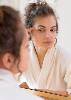 鏡を見て、美容顔のルーチンをしている女性