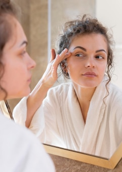 Женщина смотрит в зеркало и делает рутину красоты лица