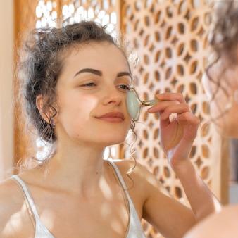 Женщина смотрит в зеркало и делает массаж лица