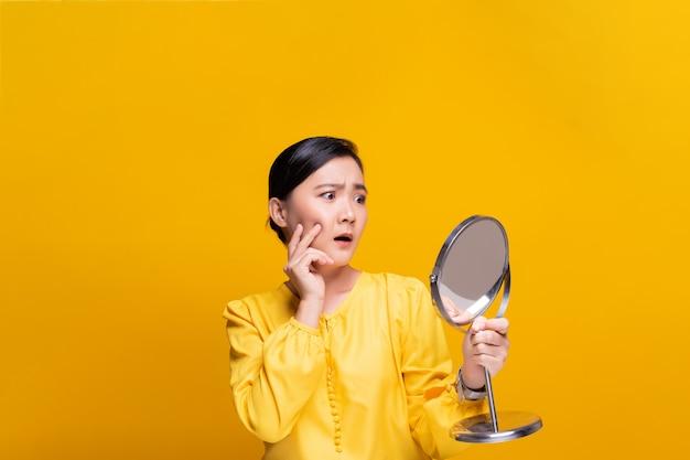 鏡を見て、彼女の顔にしわを心配している女性