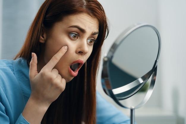 Женщина смотрит в зеркало косметики личной гигиены