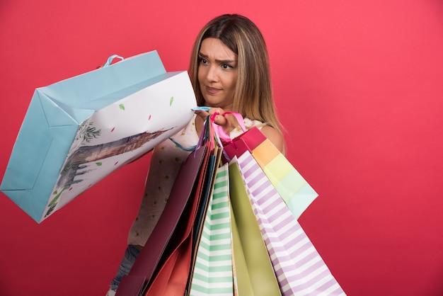 빨간 벽에 그녀의 쇼핑백 안에 찾고 여자.