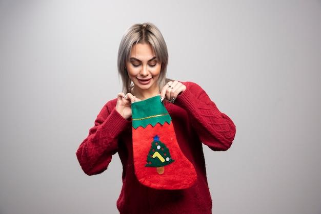 회색 배경에 크리스마스 스타킹 내부를 보고 있는 여자.