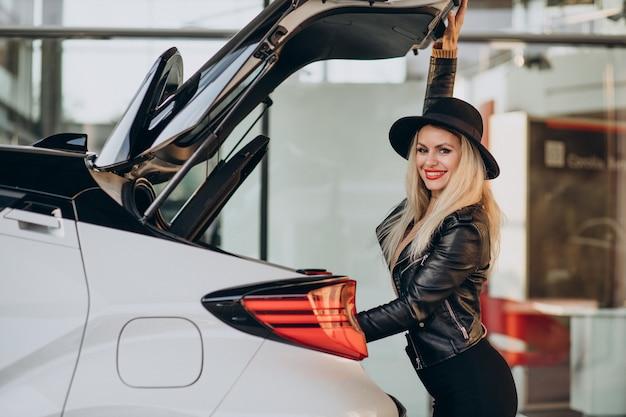 Женщина смотрит в багажник своей машины