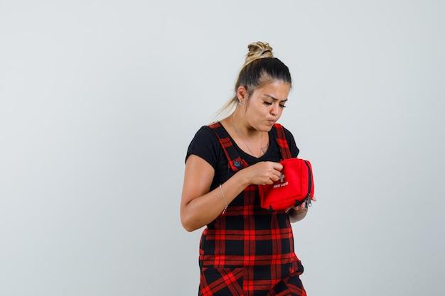 ピナフォアドレスで応急処置キットを調べて、好奇心旺盛な正面図を探している女性。
