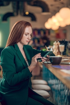 Woman looking into smartphone in cafe
