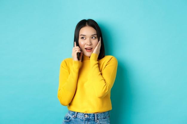 휴대 전화로 이야기하는 동안 호기심을 찾는 여자는 파란색 배경 위에 서있는 통화 중에 흥미로운 제안을받습니다.