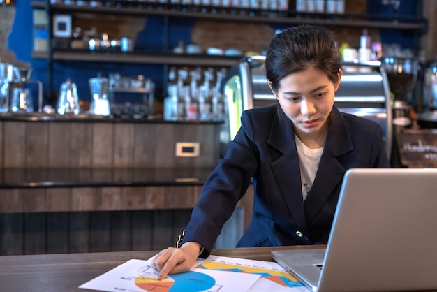 Woman looking at laptop and graph paper with energetically in coffee shop