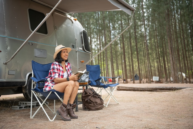 Woman looking at laptop near the camping. caravan car vacation. family vacation travel, holiday trip in motorhome. woman reading a book inside the car trunk. female learning on travel break, laying
