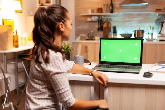 Woman looking at laptop with green mockup during night time in home kitchen. sitting at desk works on computer late at night, business, online, smart, blank, copyspace.