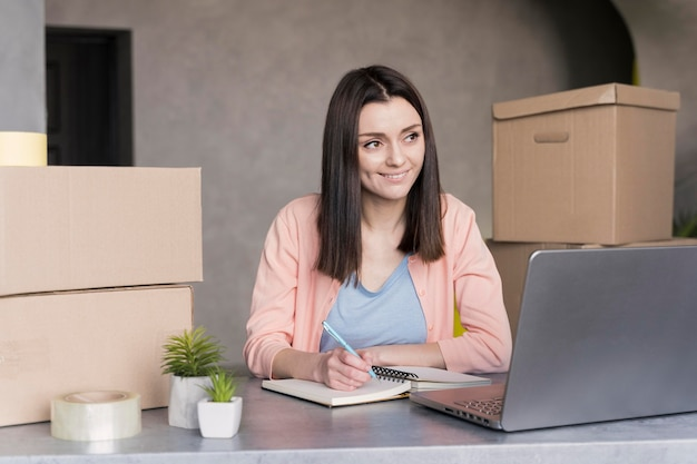 Woman looking at laptop and writing down orders to deliver