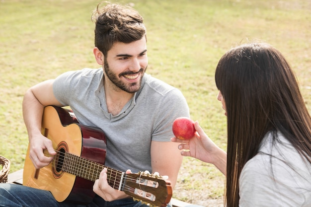 Woman looking at man playing guitar in the park