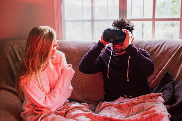 Woman looking at man in vr goggles