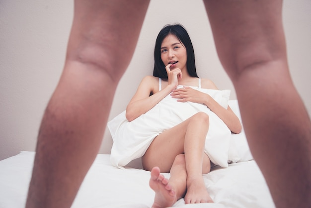 Woman in looking at mans penis in the bedroom