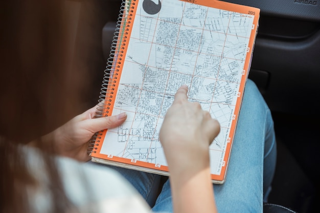 Woman looking at map in car