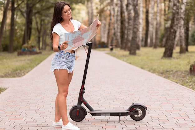 Woman looking at map next to electric scooter