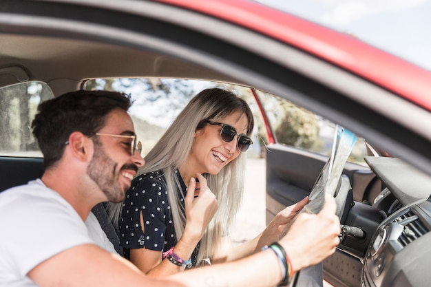 Woman looking at map hold by his boyfriend sitting in the car