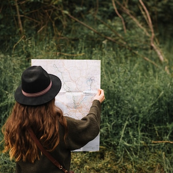 Woman looking at a map in nature