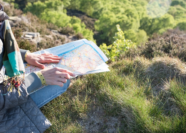Woman looking at the map and sitting on the top of mountain against an english landscape